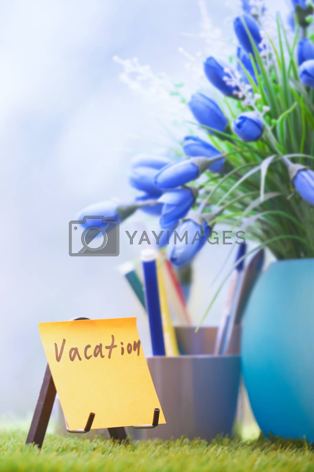 Adhesive note with Vacation text at green office