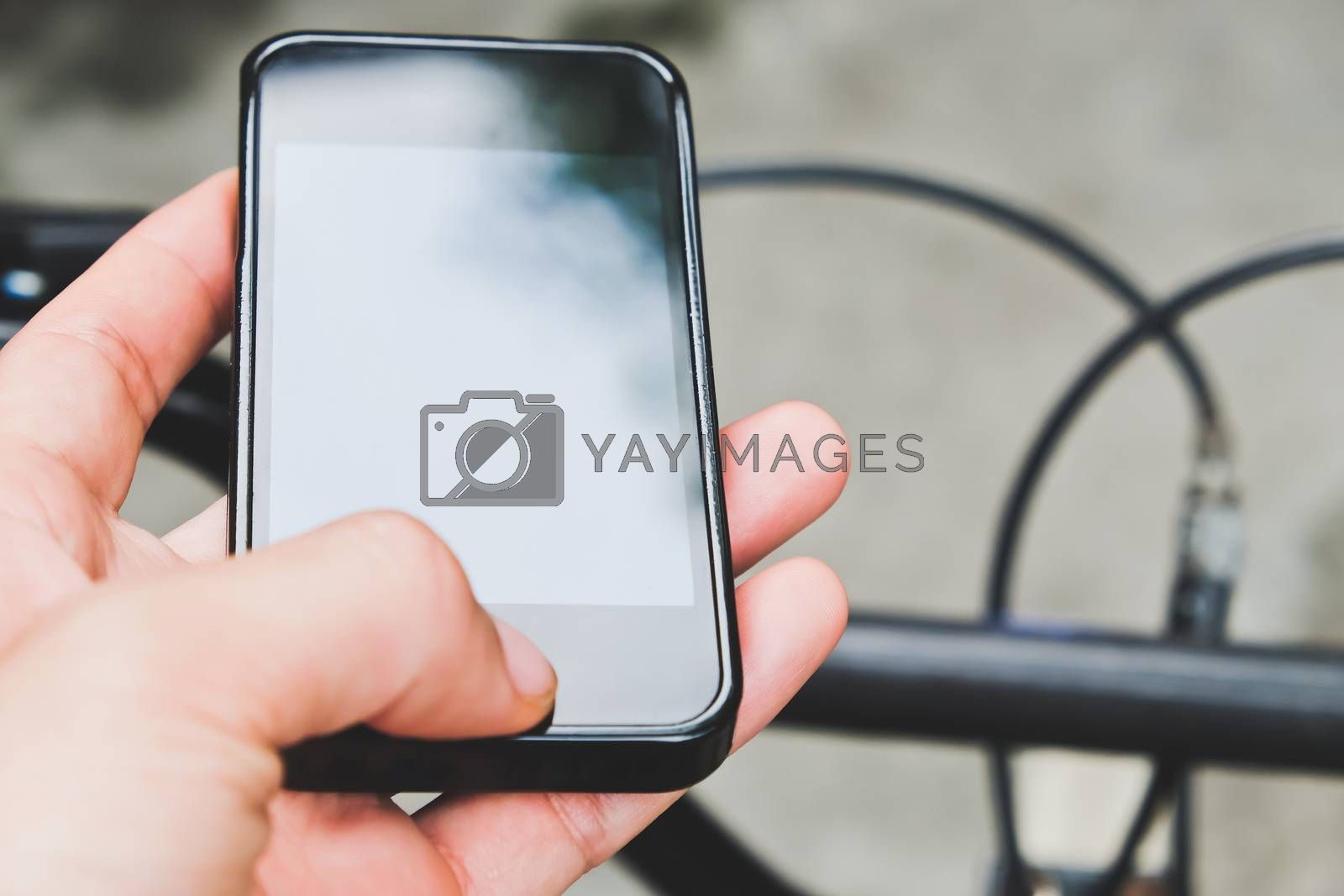 Close up image of man hand with bicycle texting on mobile phone