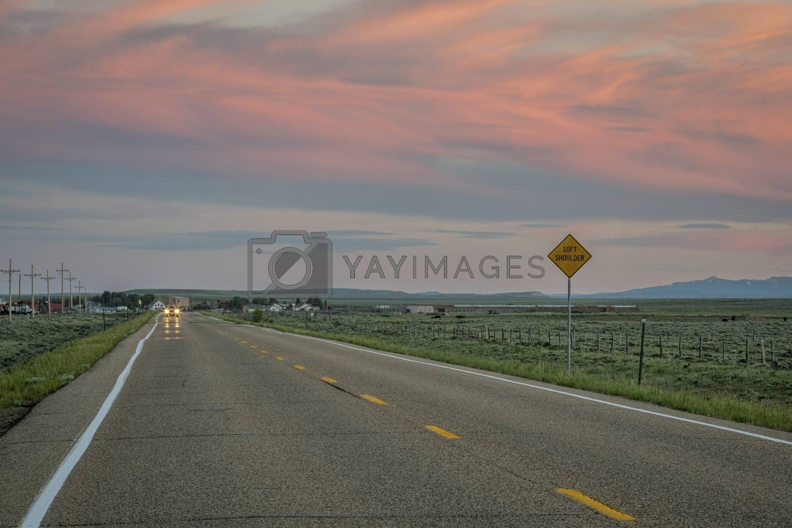 highway at dusk with pink sky near Cowdrey, North Park, Colorado