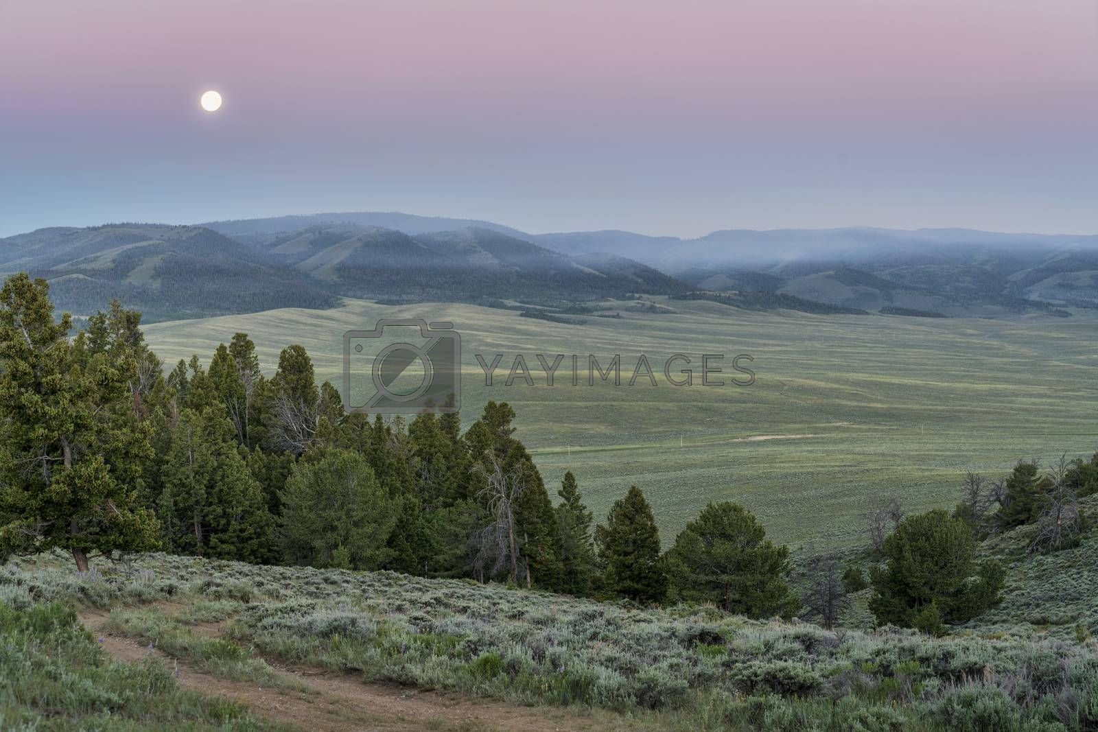 full moon setting at dawn over mountains covered by wildfire smoke - North Park, Colorado near Wyoming border (june 20, 2016)