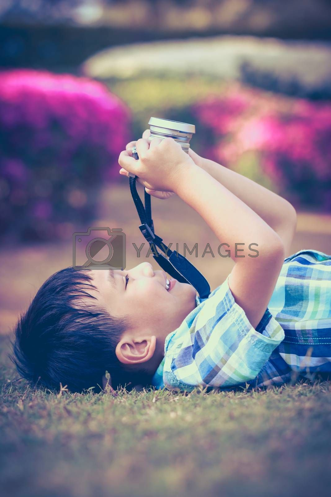 Handsome asian boy taking photo by vintage film camera, exploring nature at park, on summer in the day time. Child in nature, outdoors. Active lifestyle, curiosity, pursuing a hobby concept. Vintage.