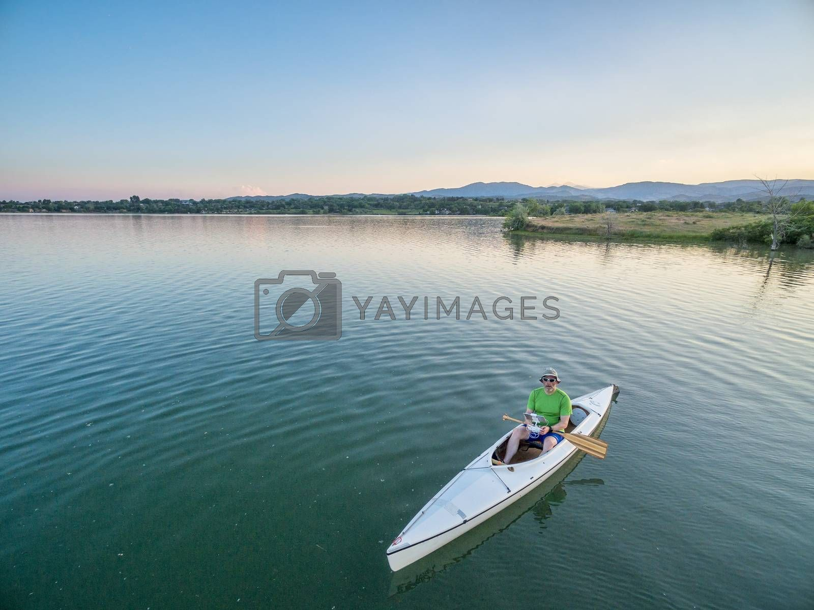 male paddler is operating a drone from a canoe on a lake, aerial view