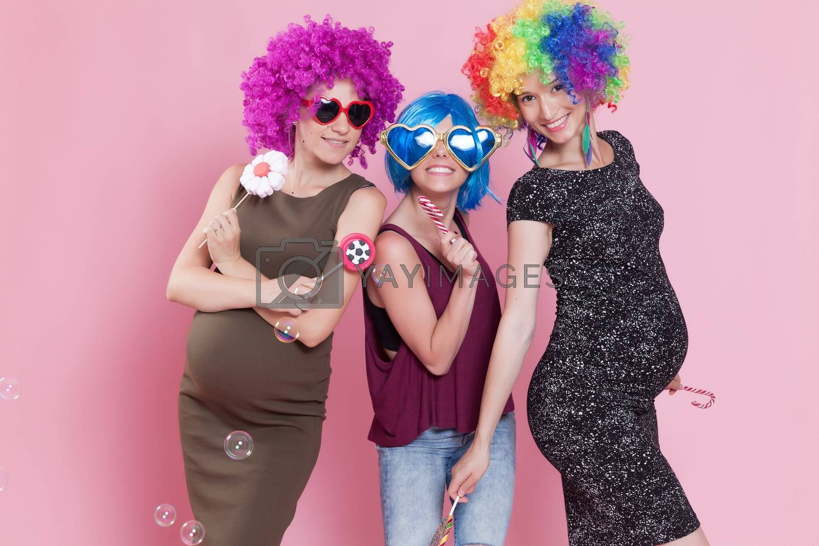 Group of young women disguised for a party, with candies, ballons and wigs.