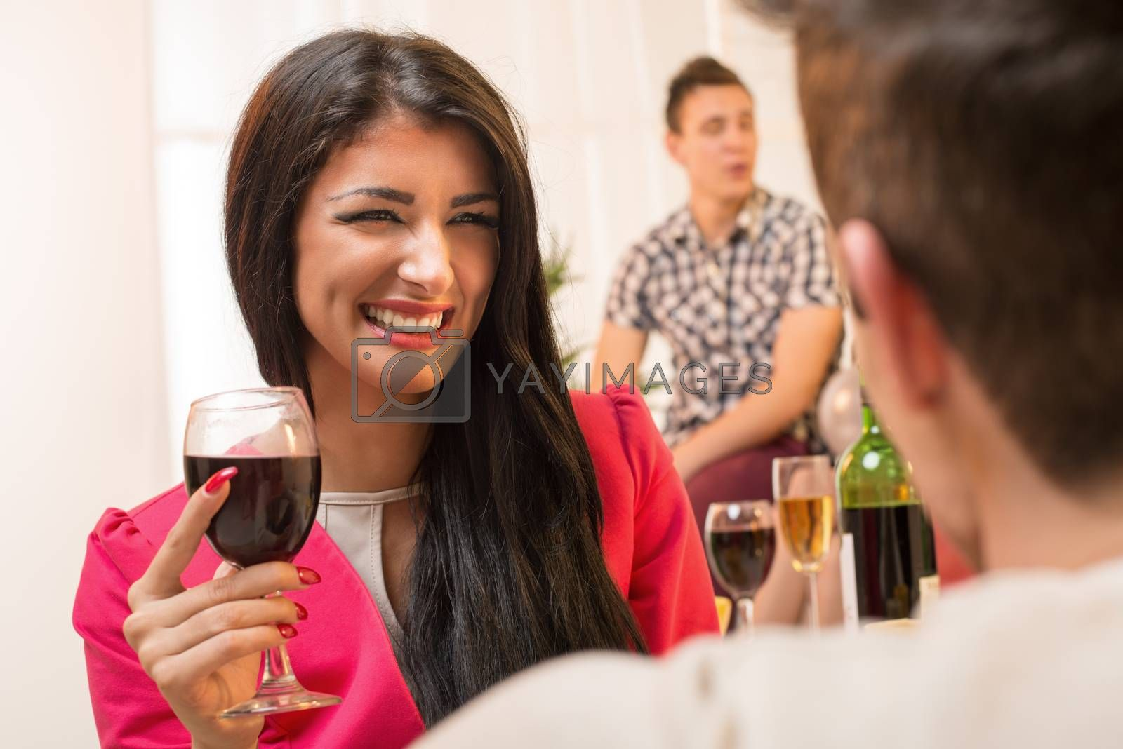 Young pretty brunette girl with a glass of wine in hand, with a smile looking at the guy who has his back turned to the camera, while in the background see another young guy in the ambient house party.