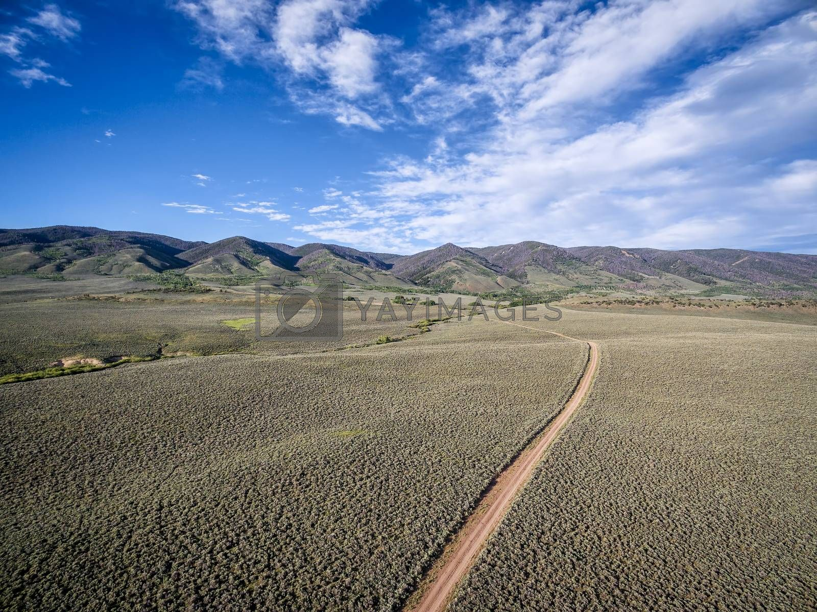 ranch road and Medicine Bow Mountains in North Park near Walden, Colorado - aerial view