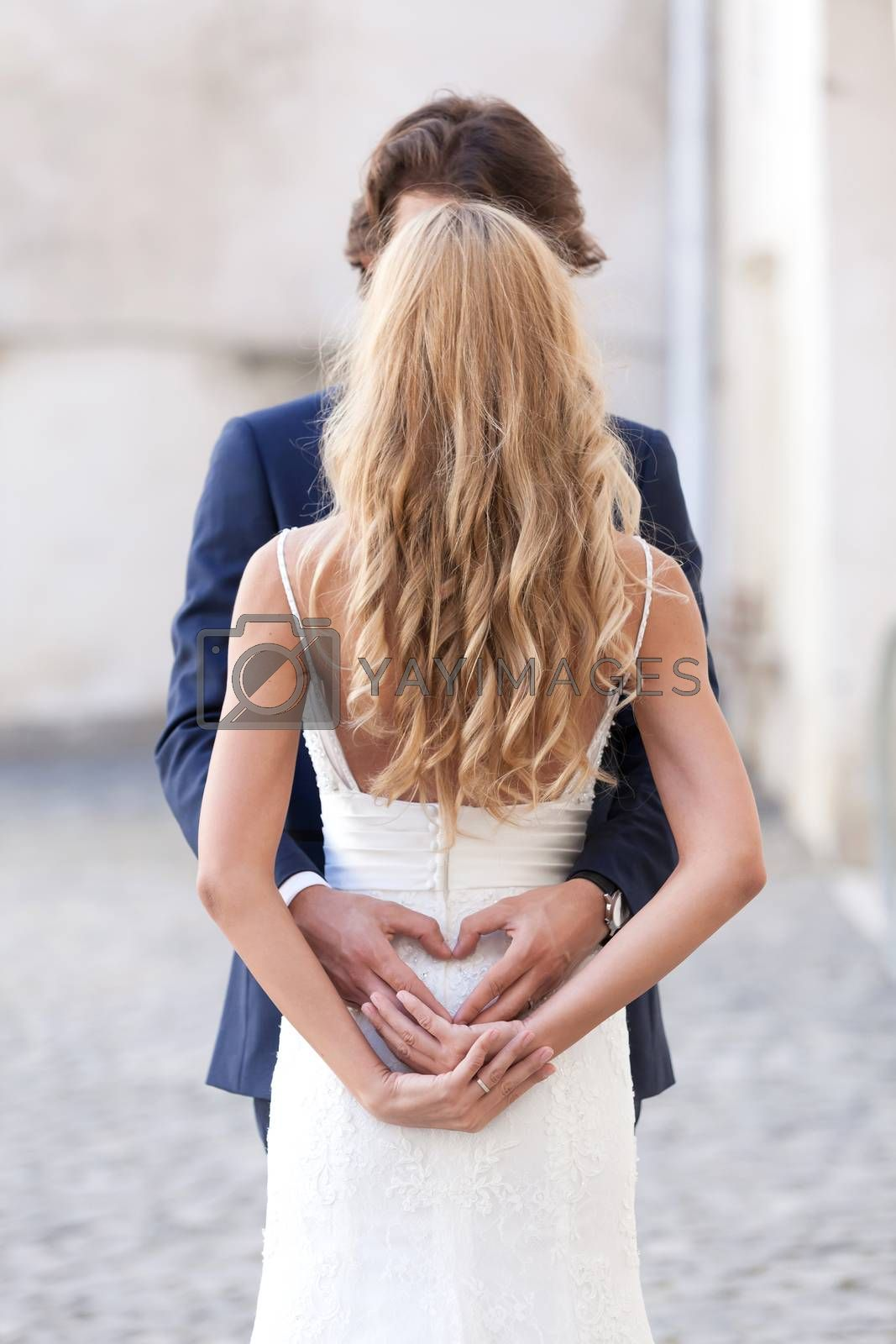 Newlywed couple holding each other, forming a heart with their hands.