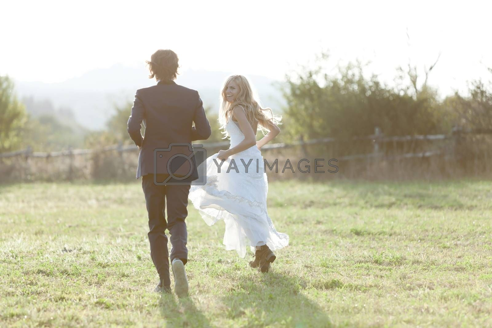 Married couple running in a field, having fun and smiling. She is looking back.