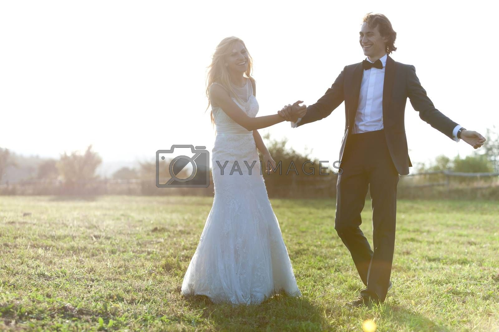 Beautiful married couple having fun and smiling on a field.