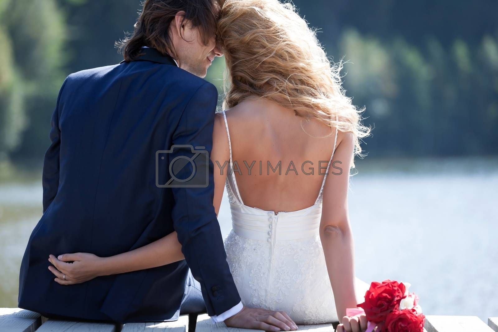 Beautiful couple relaxing on a foot bridge, near a lake, acting very romantic