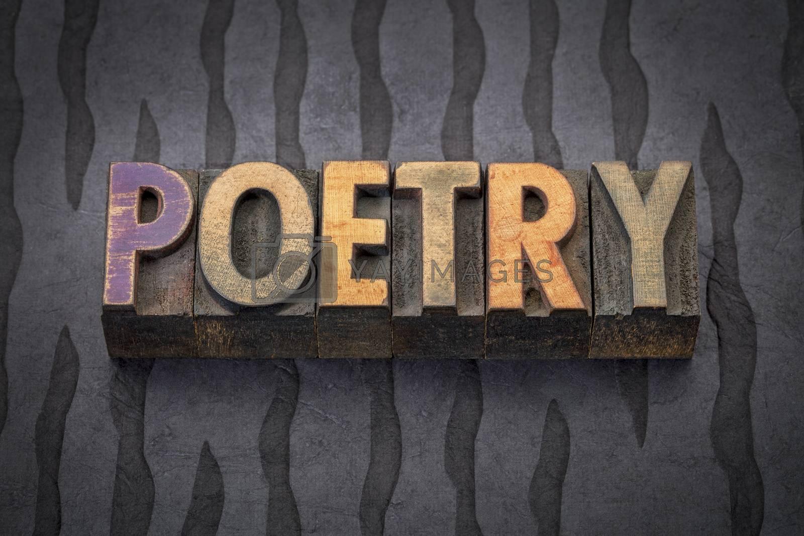 poetry word - text in vintage letterpress wood type blocks against black Nepalese lokta paper