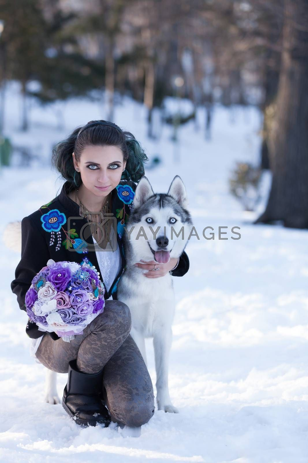 Young girl portrait with lovely big eyes holding a paper flower bouquet while is embracing a husly dog.