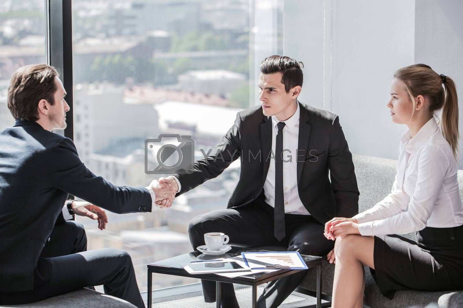 Business people sitting near panoramic window with view on city and talking