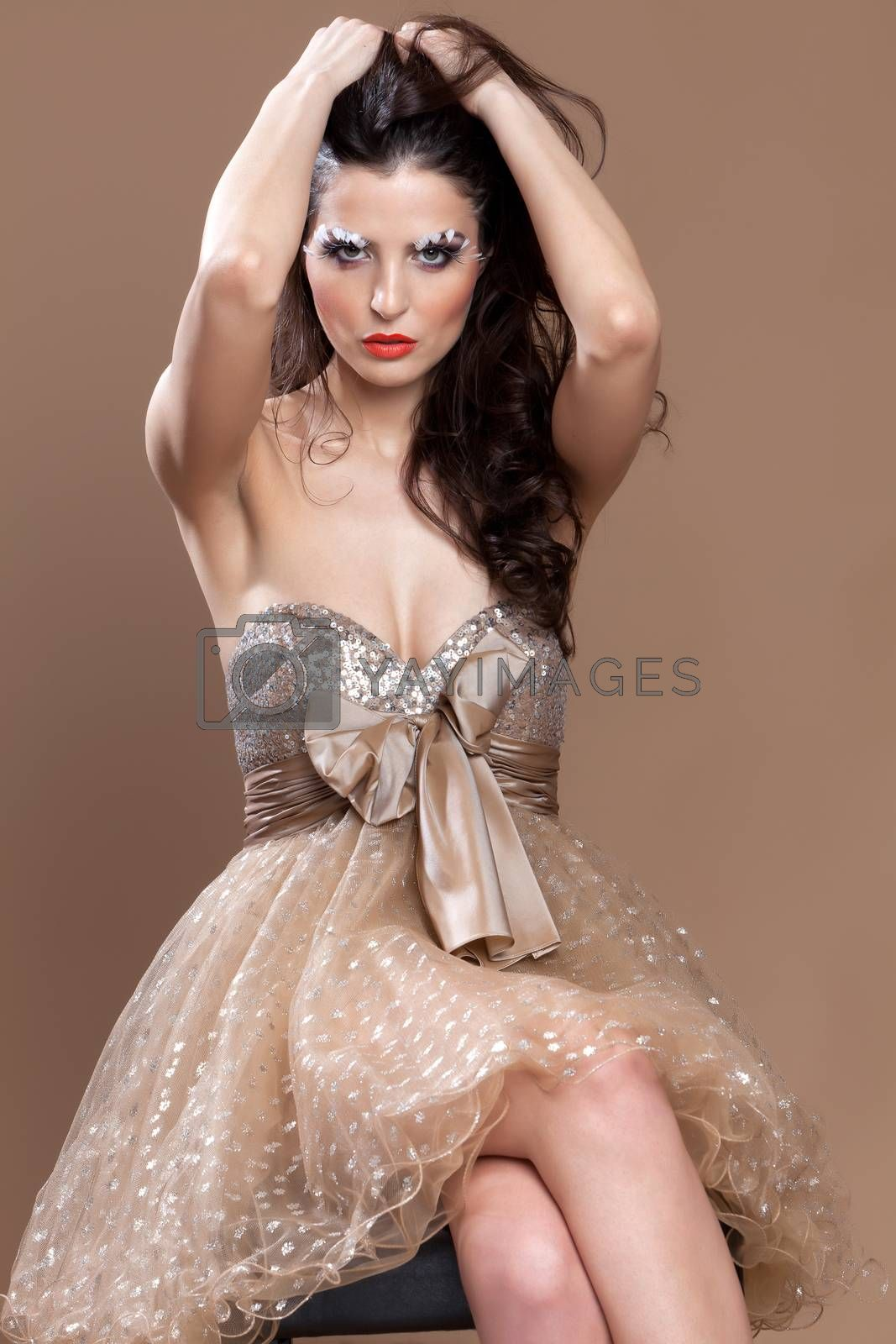 Stunning beautiful brunette sitting in a chair and dressed in an elegant dress, arranging gracefully her hair.