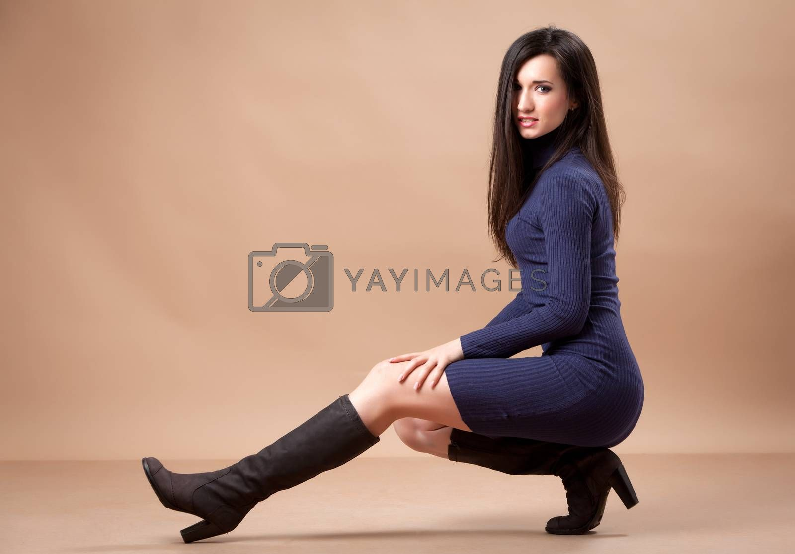 Pretty girl sitting on heels while is looking at camera.