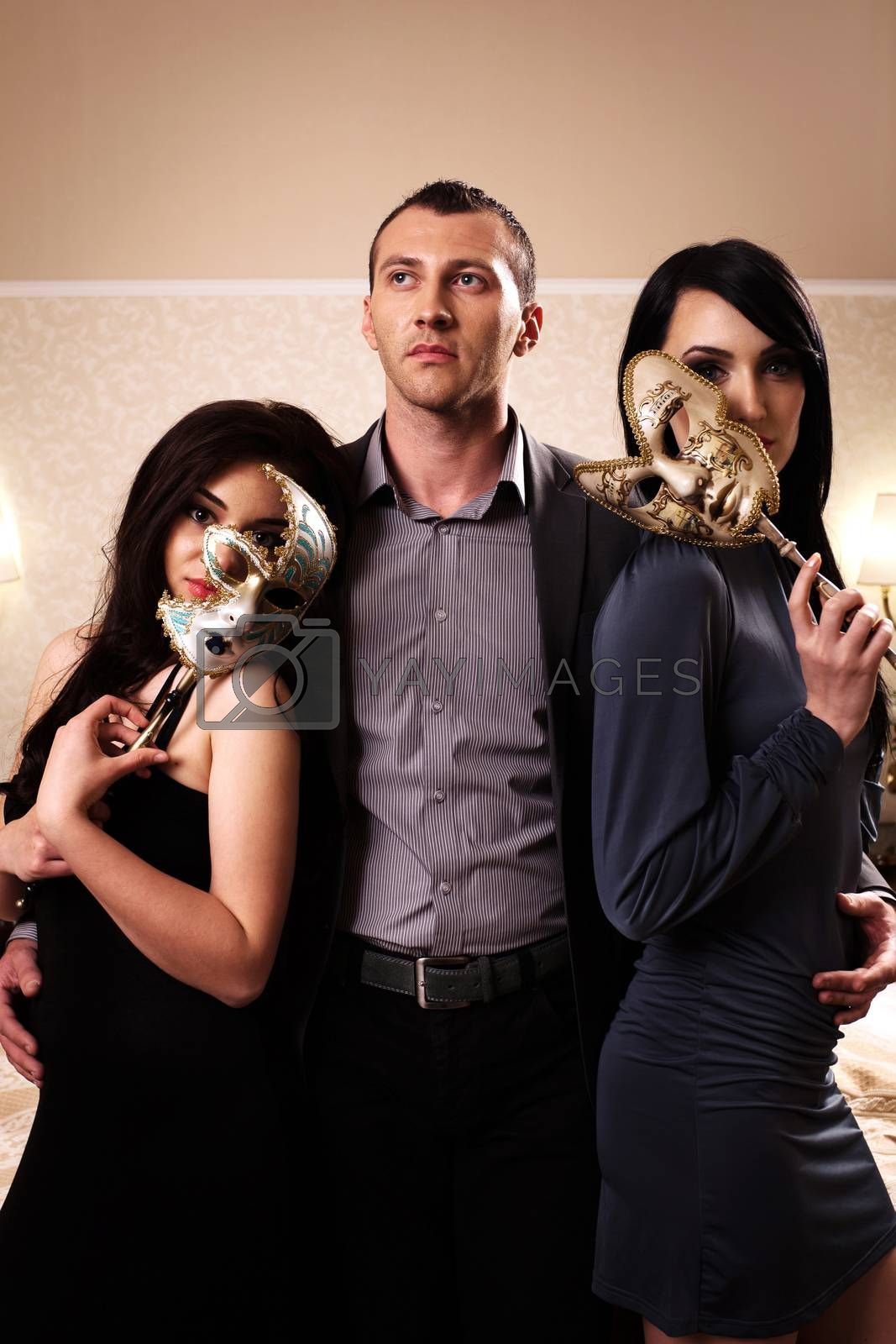 A man with two ladies wearing masks. See more images from the same shoot.