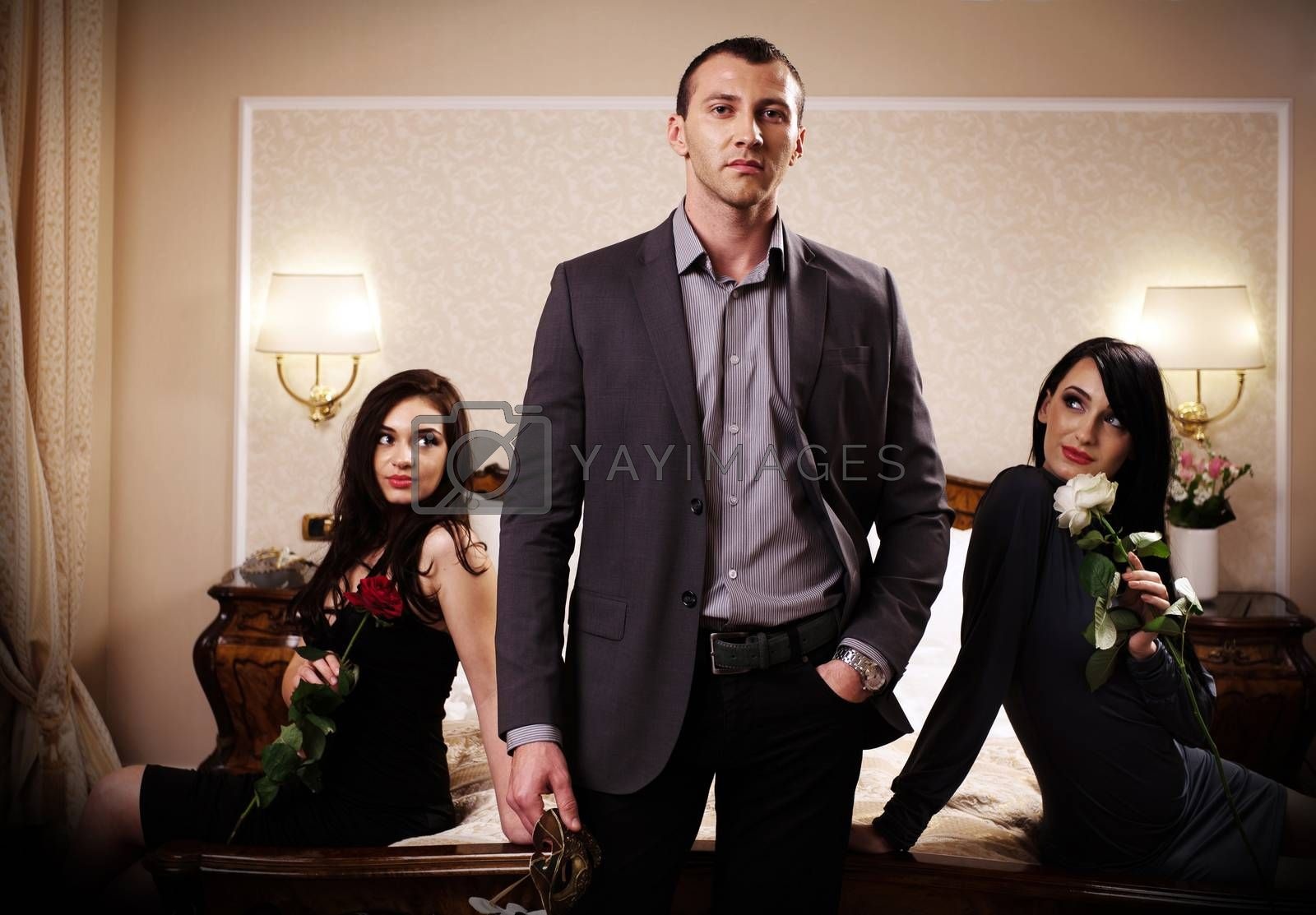 A man with a mask standing in front of two ladies. See more images from the same shoot.