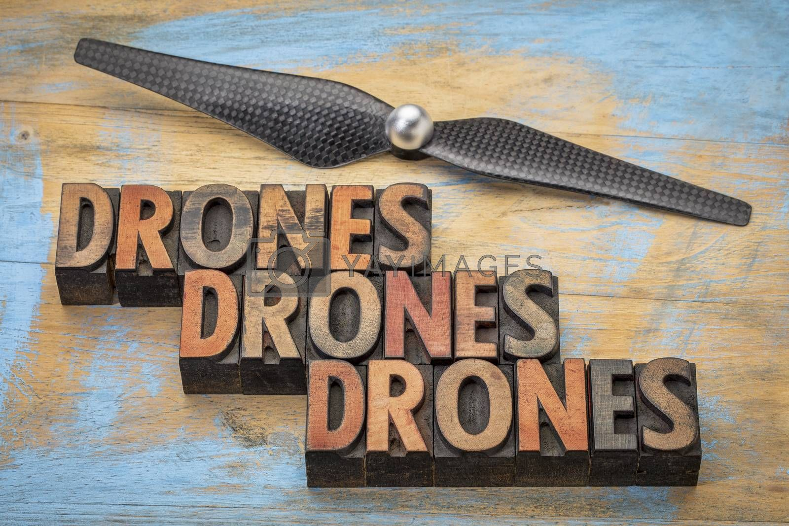 drones word abstract in vintage letterpress  wood type with a drone propeller - new aircraft technology concept
