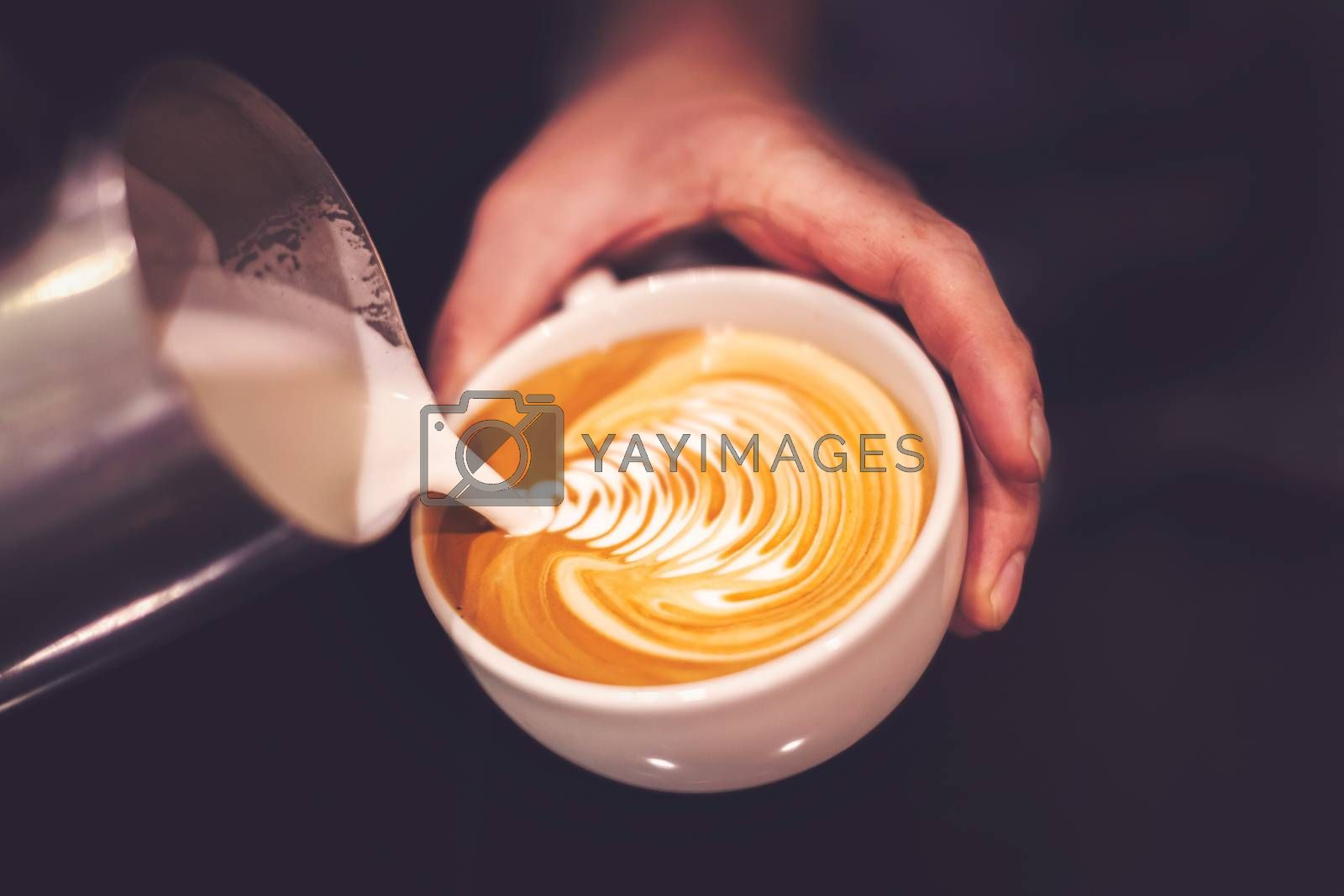 Barista pouring coffee into a cup creating beautiful pattern