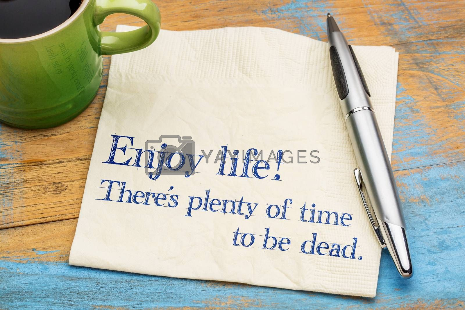 Enjoy life! There is plenty of time to be dead. Handwriting on a napkin with a cup of coffee,