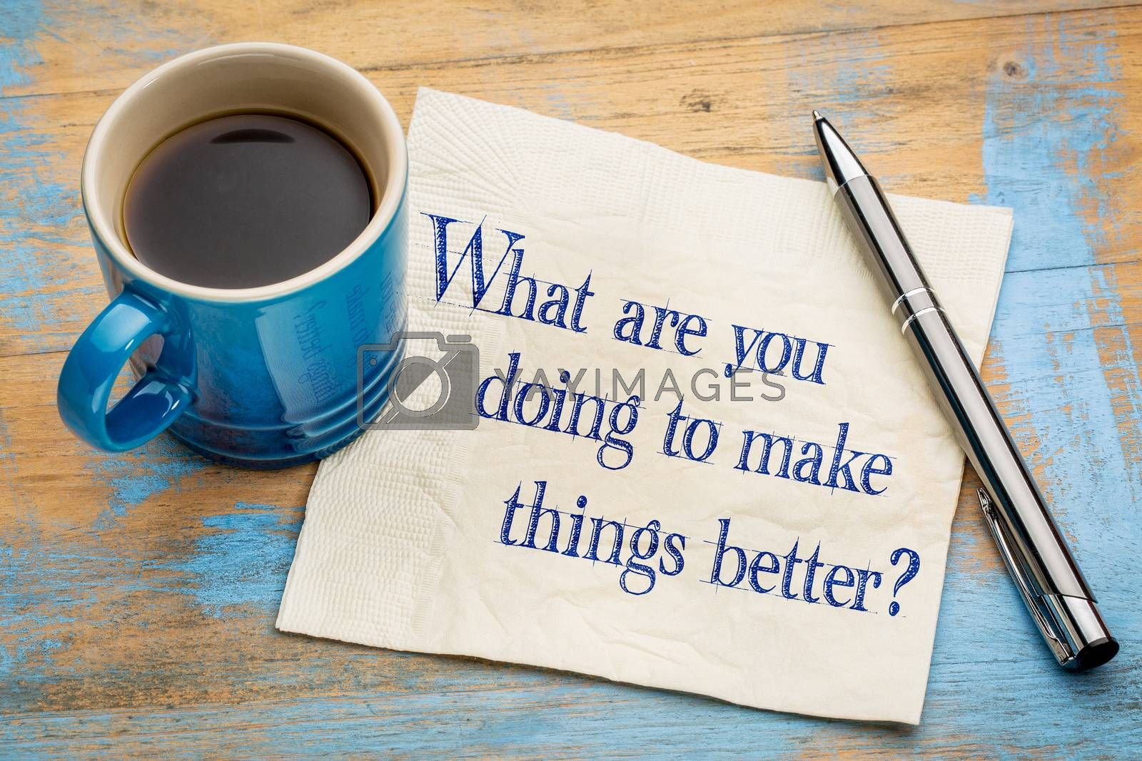What are you doing to make things better? Handwriting  on a napkin with a cup of espresso coffee