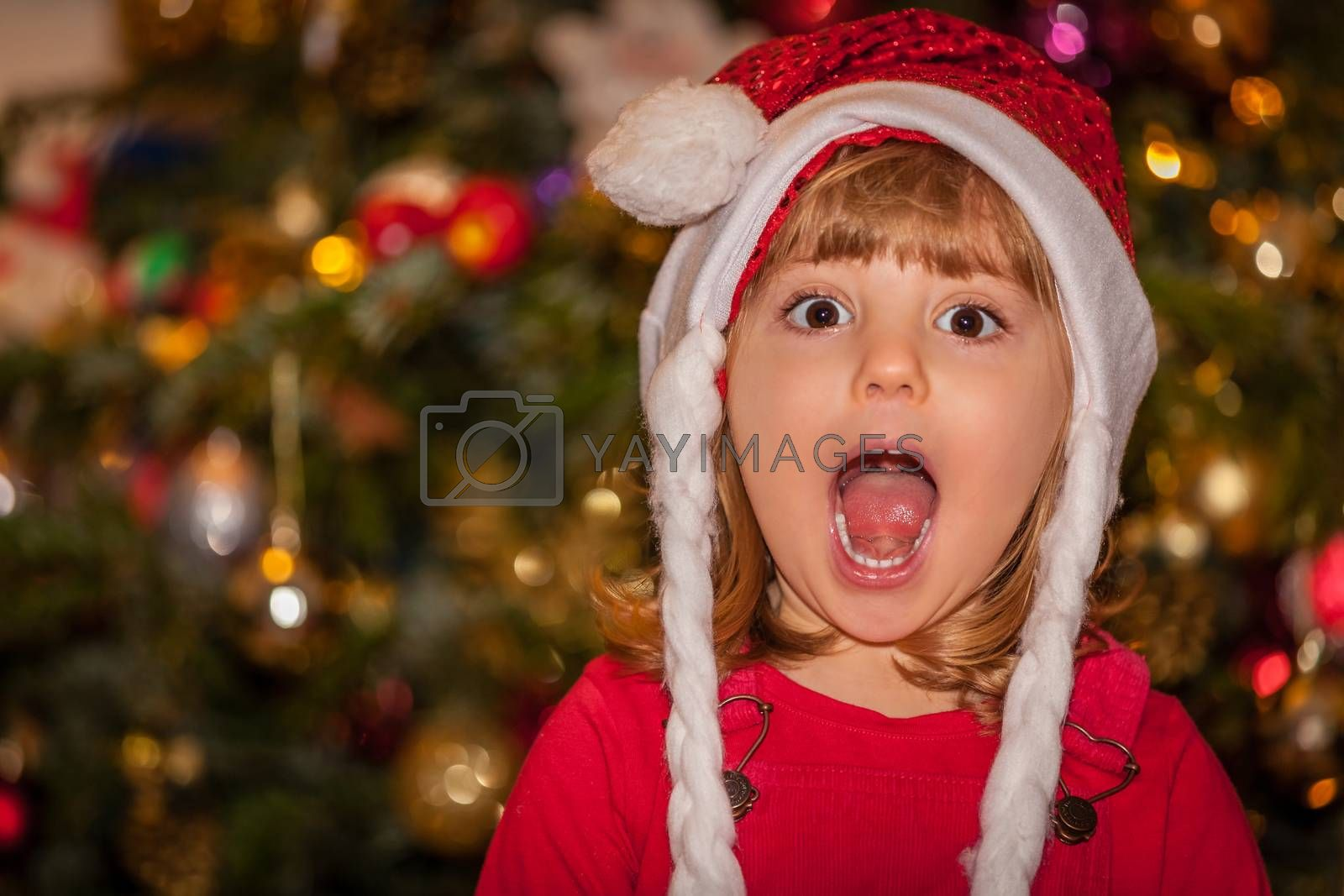 Cute Christmas girl with the Christmas tree in the background