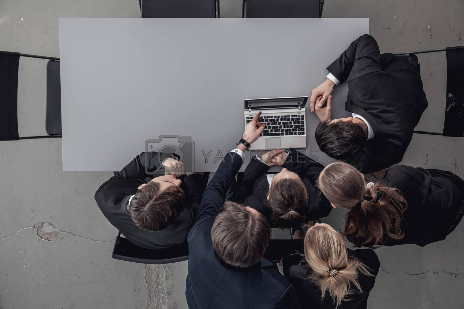 Group of business people look together at laptop in office