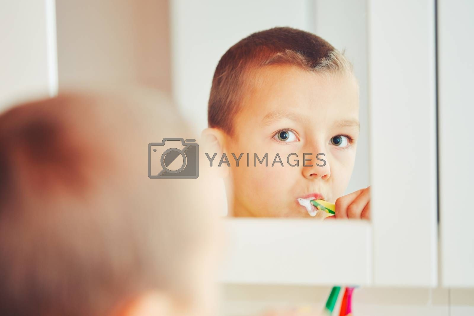 Everyday life at home. Little boy is cleaning teeth in the bathroom. - selective focus