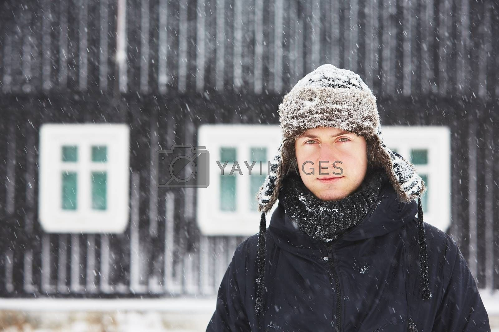 Portrait of young man outdoors in winter under snowstorm