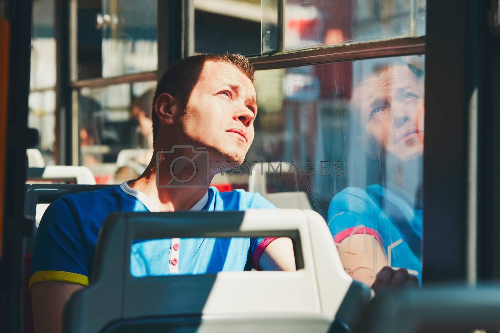 Everyday life and commuting to work by public transportation. Handsome young man is traveling by tram (bus).