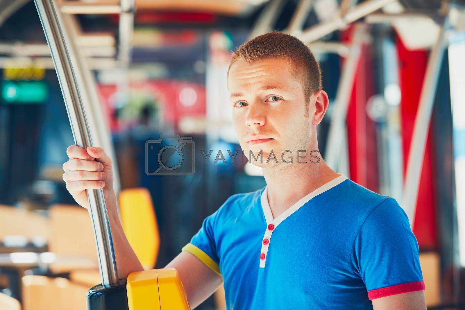 Everyday life and commuting to work by public transportation. Handsome young man is traveling by bus (tram).