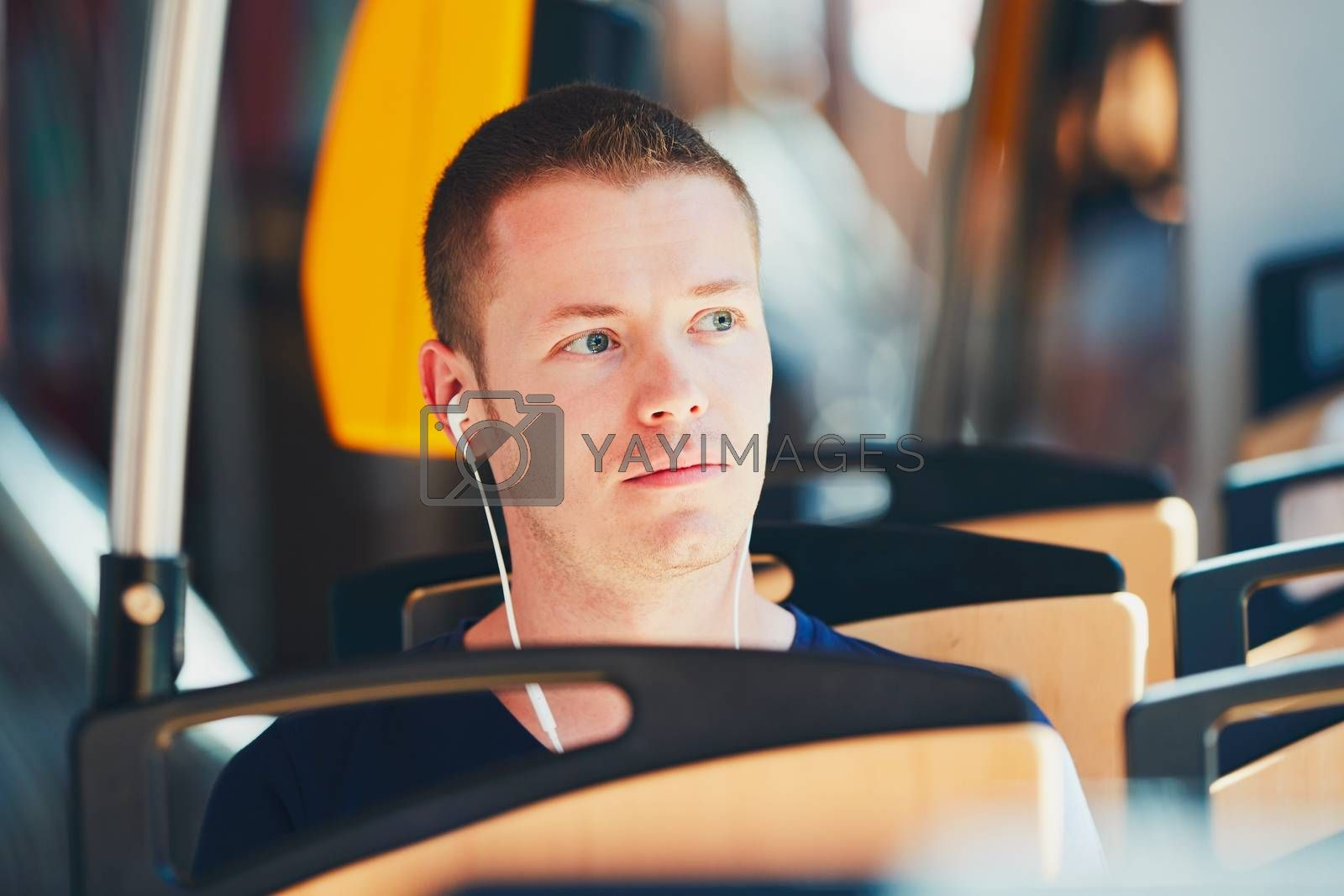 Everyday life and commuting to work by public transportation. Handsome young man is traveling by tram. Man is wearing headphones and listening to music.