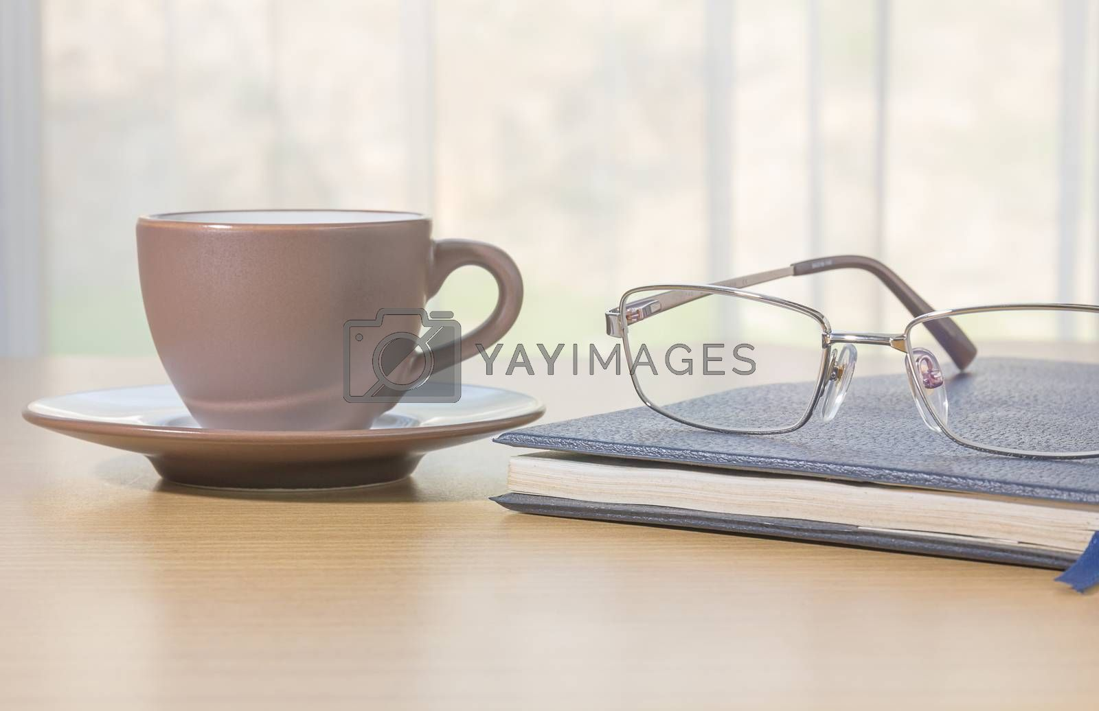 Glasses put on book and coffee cup on the desk by nature light from window