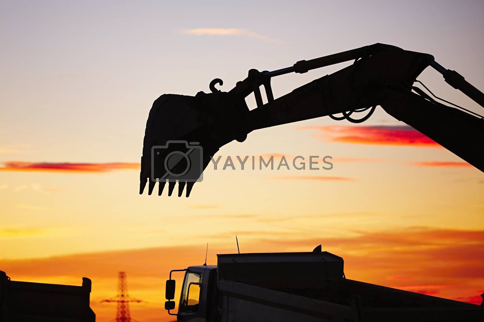 Silhouette of the backhoe in the building site