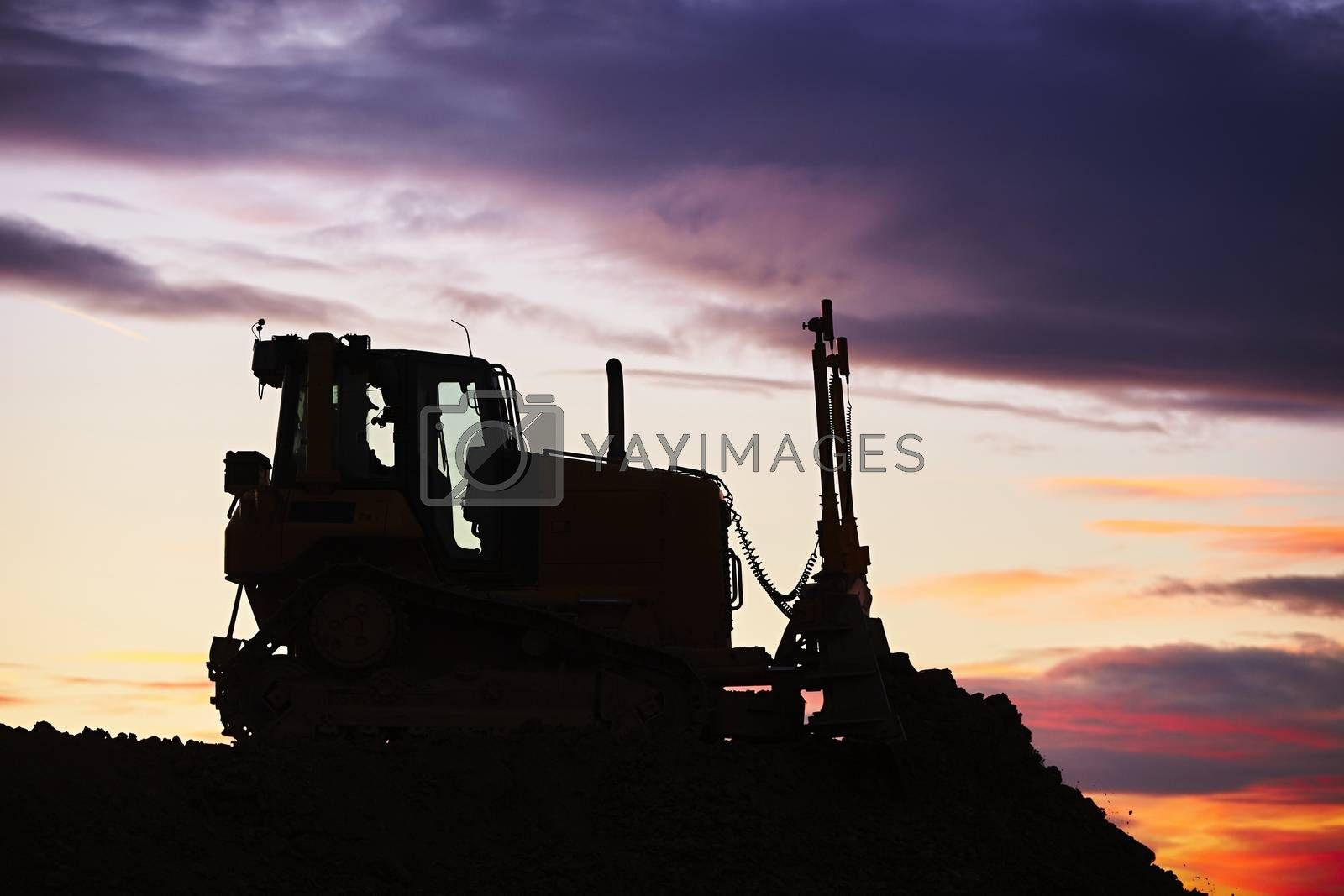 Silhouette of the bulldozer in the building site