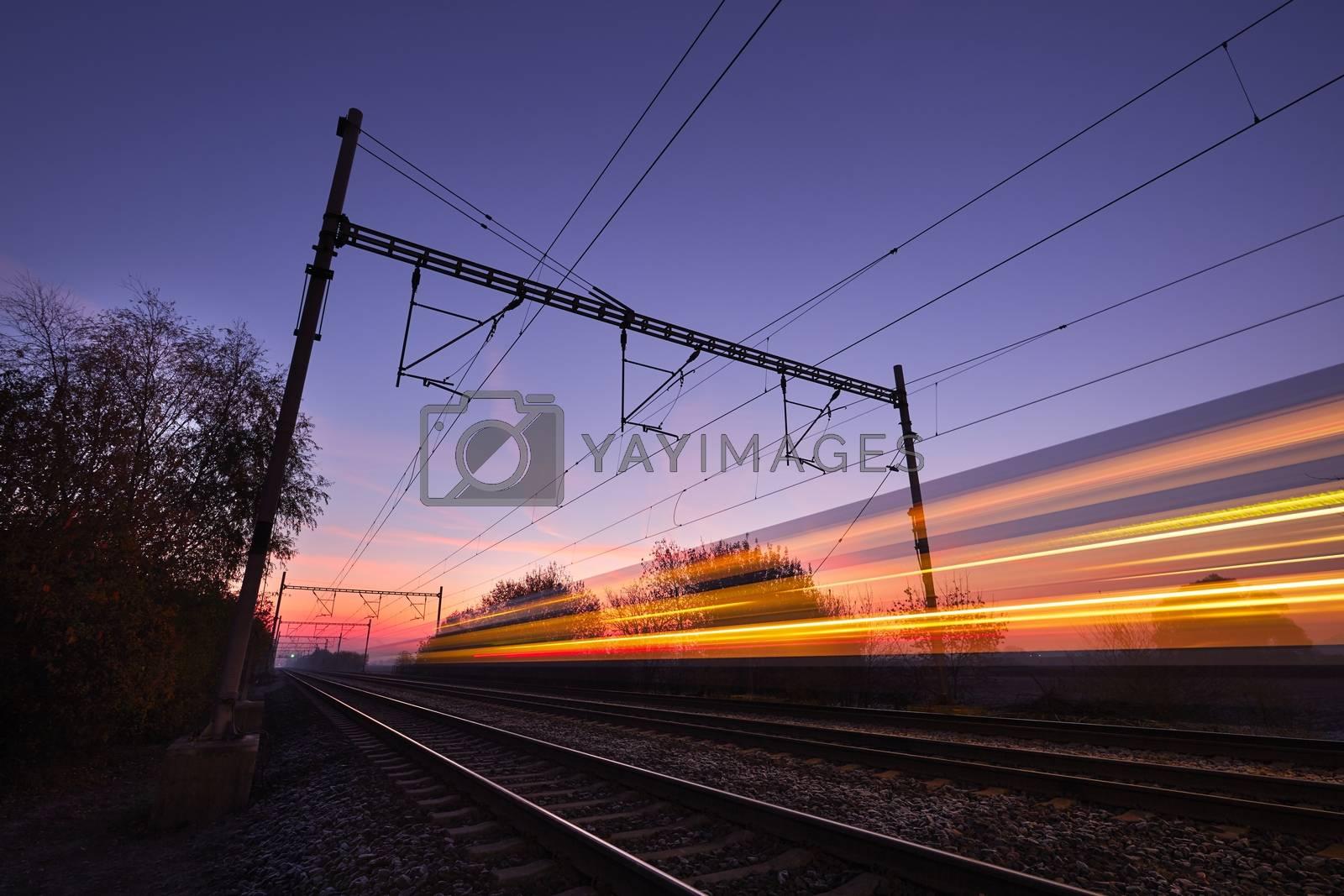 Passenger train on railroad tracks at the sunrise - blurred motion