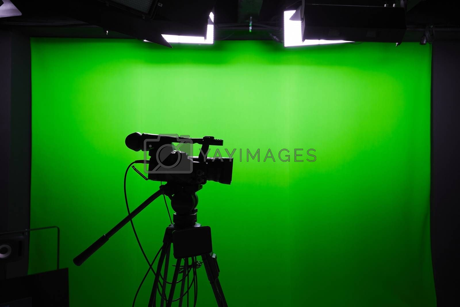 Silhouette of digital video camera in front of the green screen