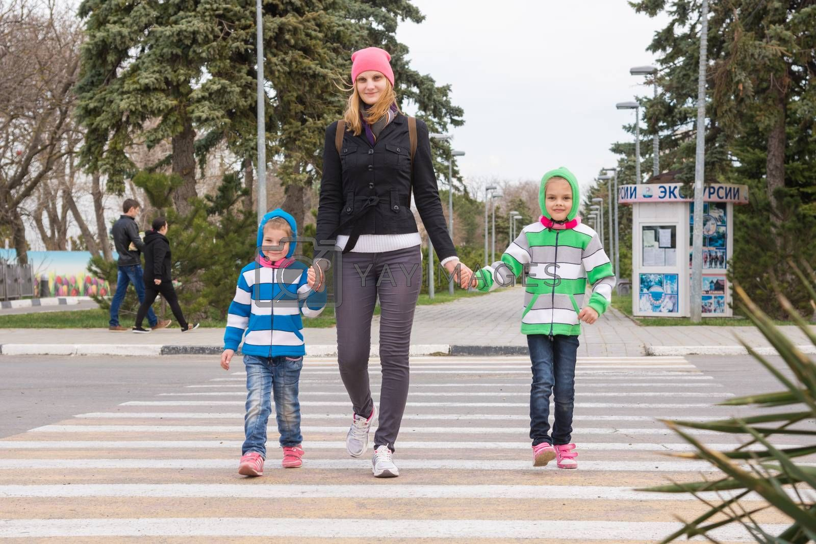 Anapa, Russia - March 9, 2016: a young mother with two daughters cross the road at a pedestrian crossing by Madhourse