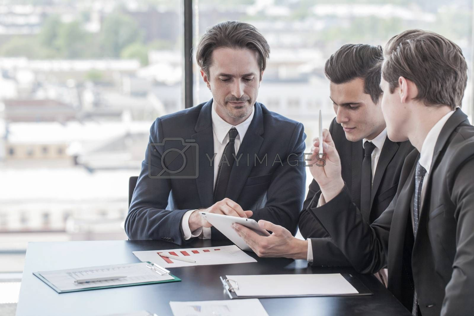 Businessmen working together in office with financial reports and digital tablet pc