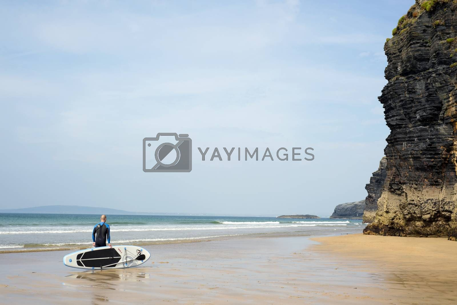 surfer standing with board on ballybunion beach in the wild atlantic way