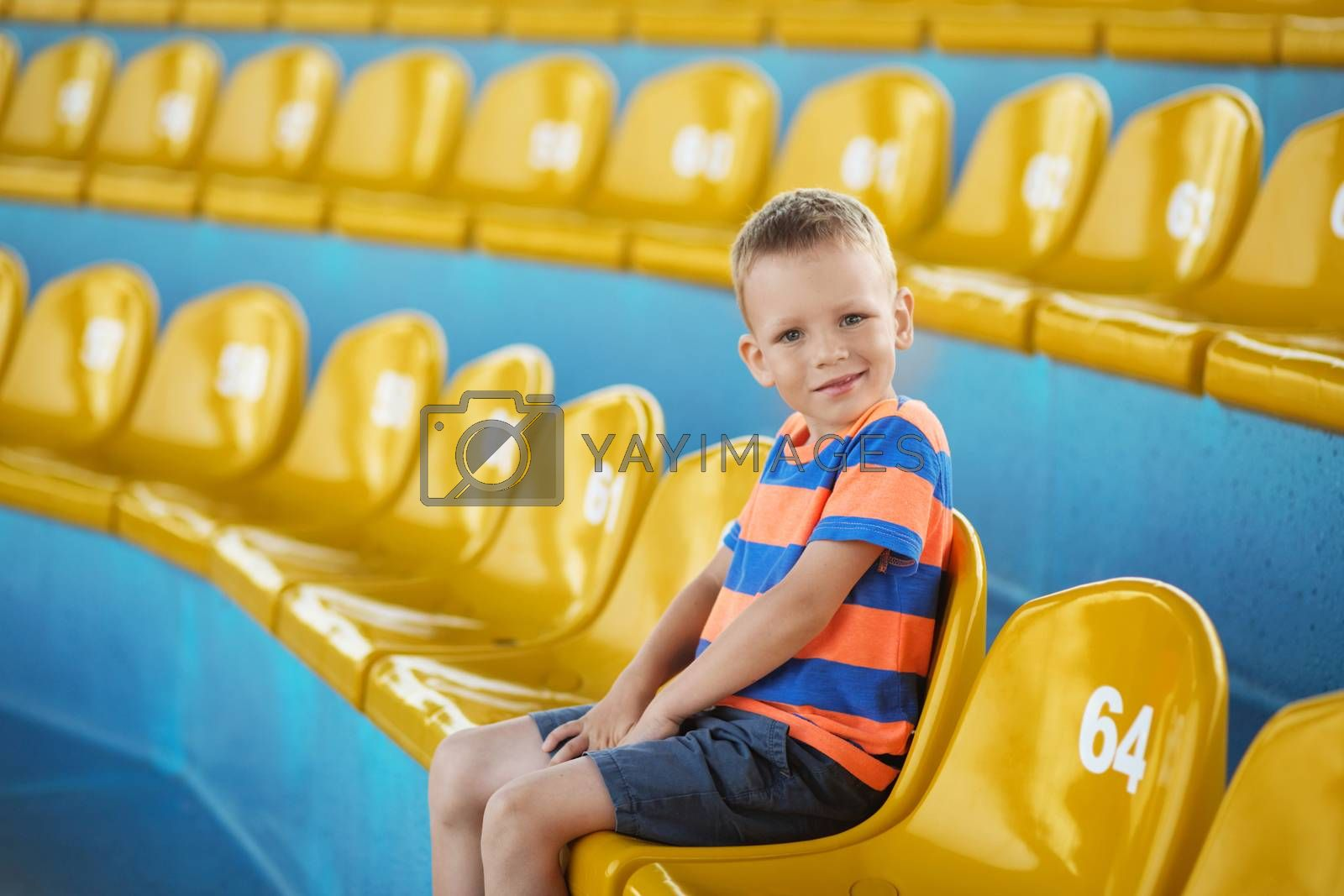Little boy sitting in an empty stadium among yellow plastic numbered seats and applauds. Child take own seat in the stadium or dolphinarium and waiting patiently when the show or game starts.