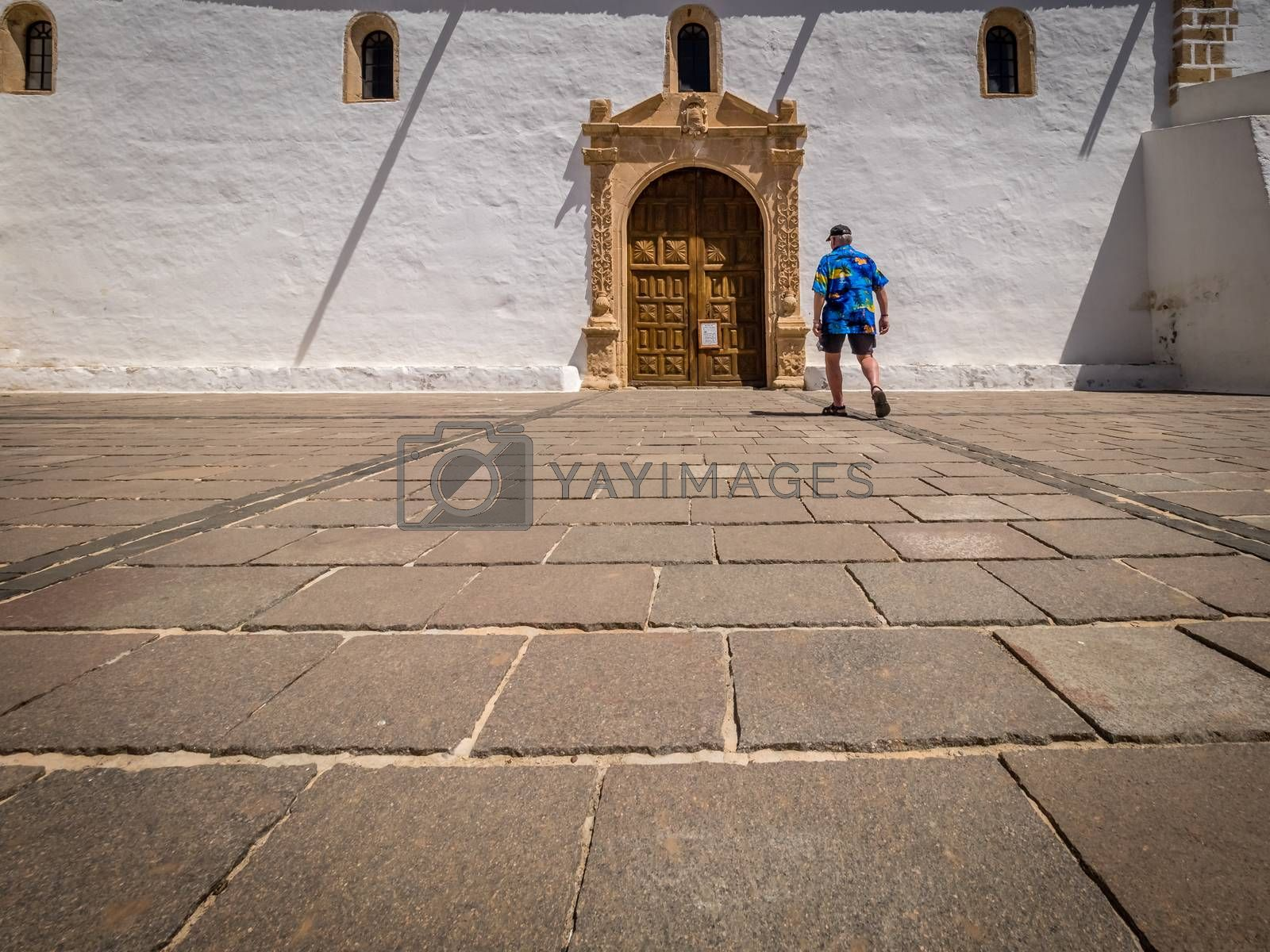 Tourist walking towards the gates of the Cathedral of St. Mary of Betancuria, Canary islands, Spain. Picture taken 13 April 2016