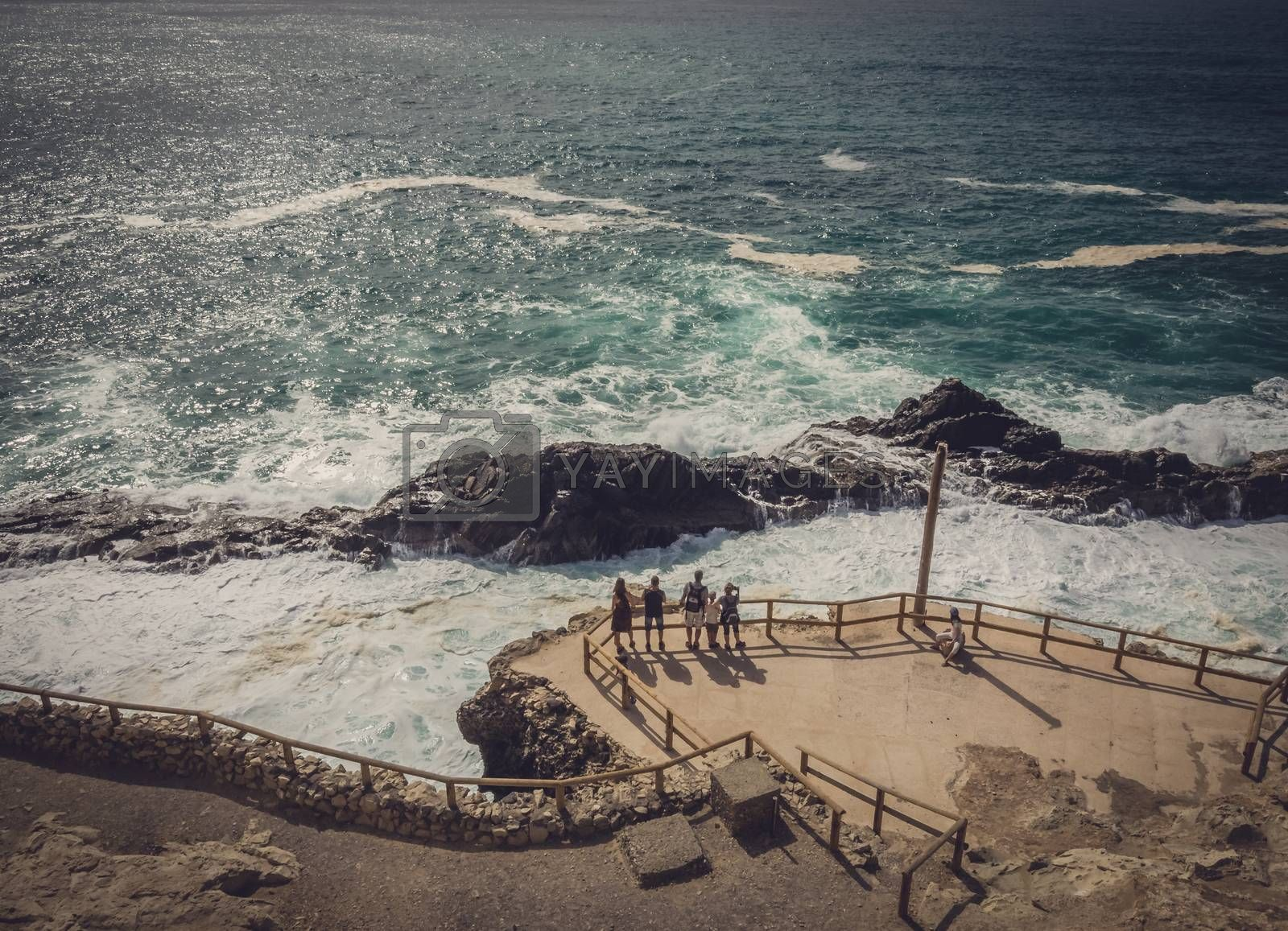 Group of tourists admiring the rocky coast in Ajuy, Parque Rural de Betancuria in Fuerteventura, Canary Island, Spain. Picture taken 13 April 2016