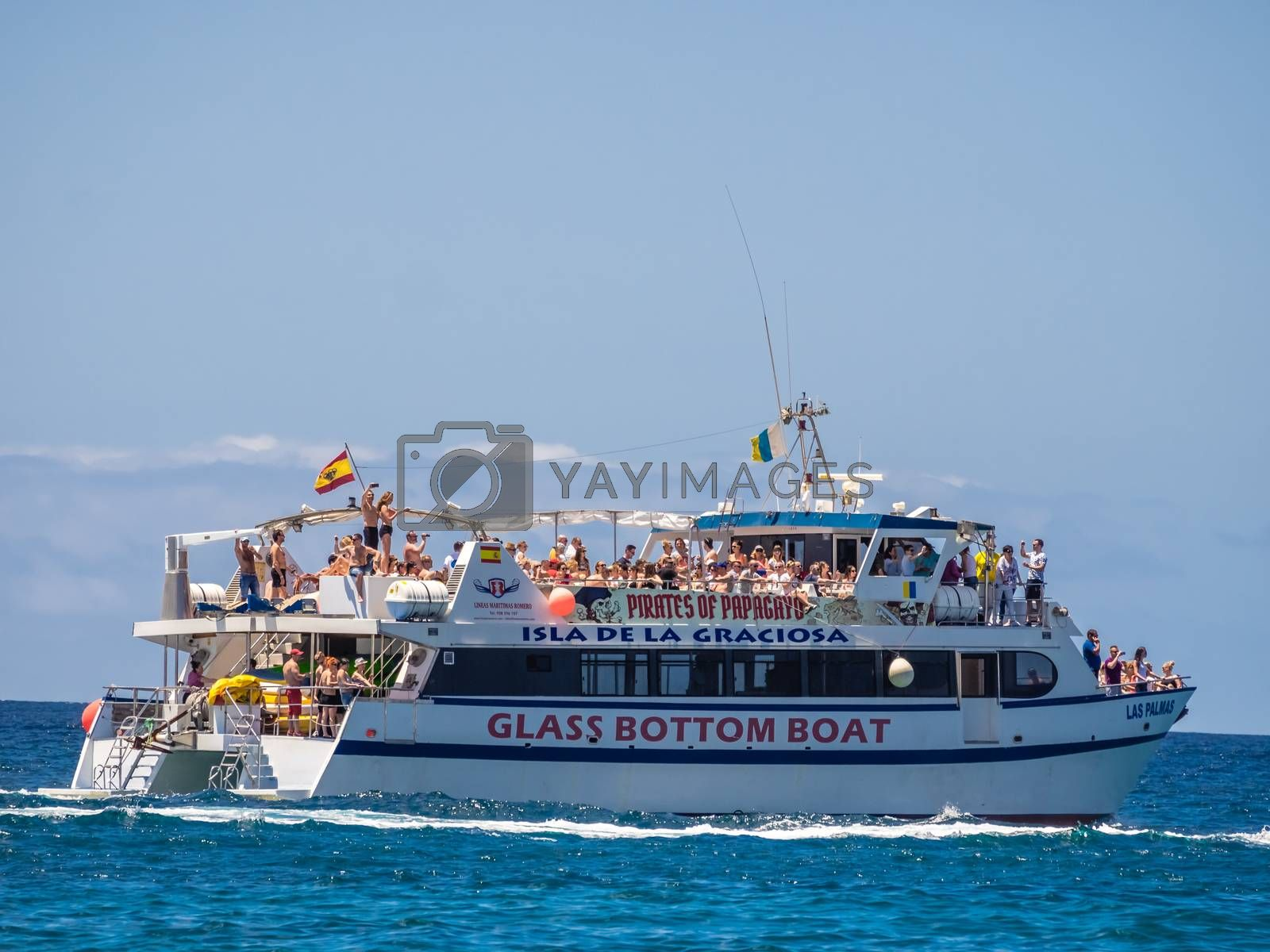 Small private party boat sailing between Lanzarote and Fuerteventura Islands in Canary Islands, Spain. Picture taken 20 April 2016.