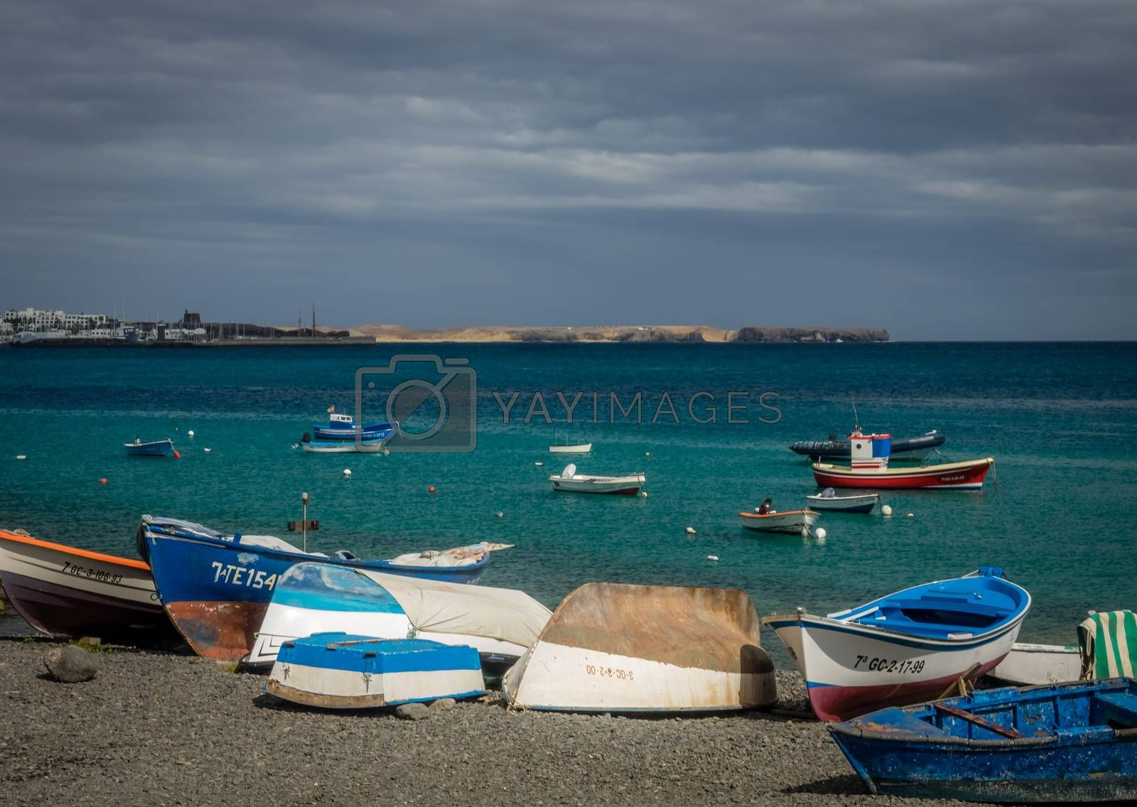 Small colorful fishermen boats on a shore in a harbour in Playa Blanca, Lanzarote, Canary Islands, Spain. Picture taken 19 April 2016
