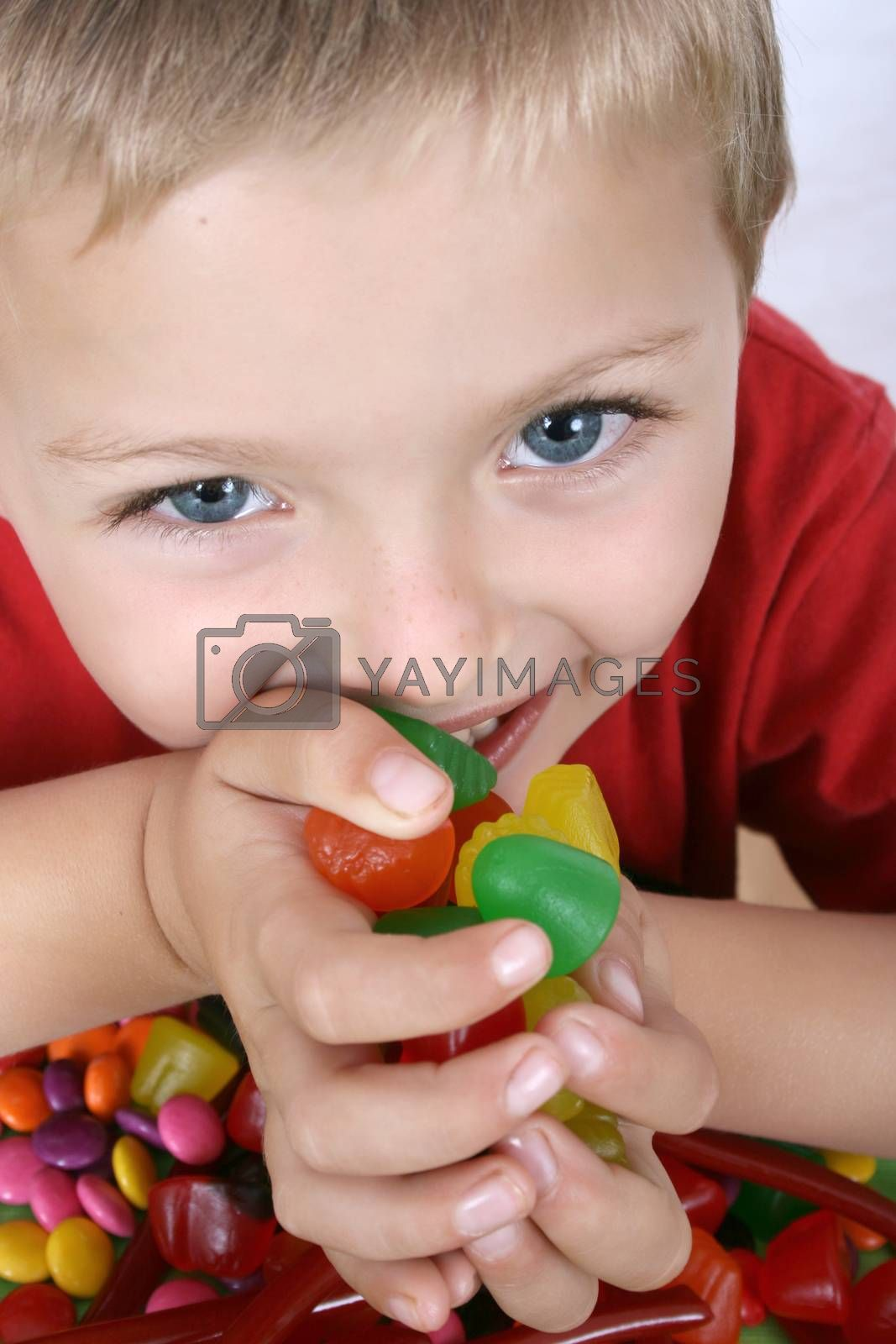 Young boy being with a table full of colorful sweets