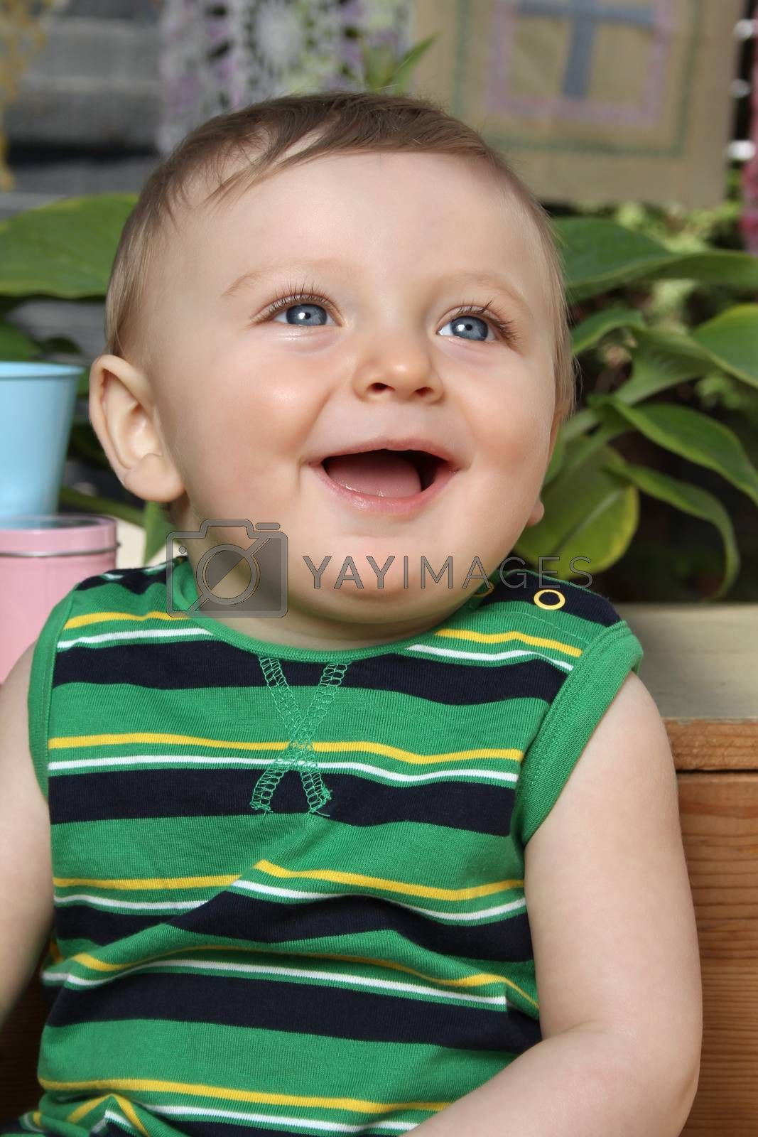 Cute baby boy outside in the garden wearing green outfit