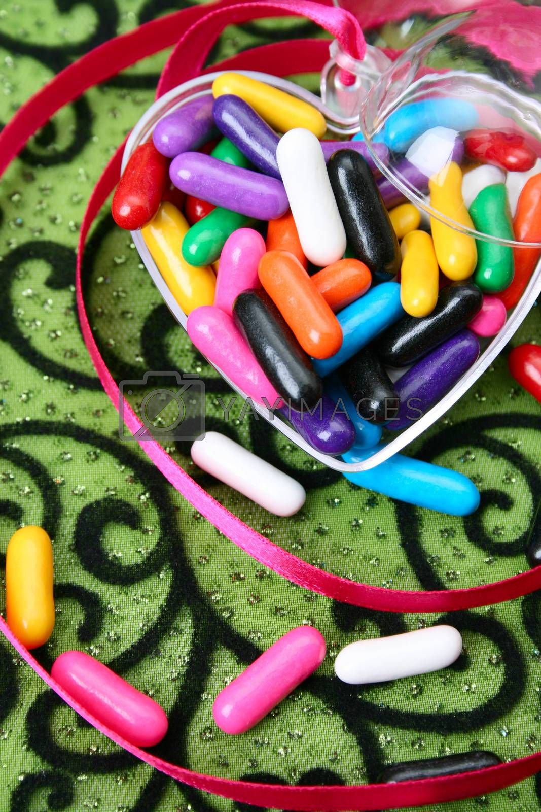 Colorful candies in a heart container on green background
