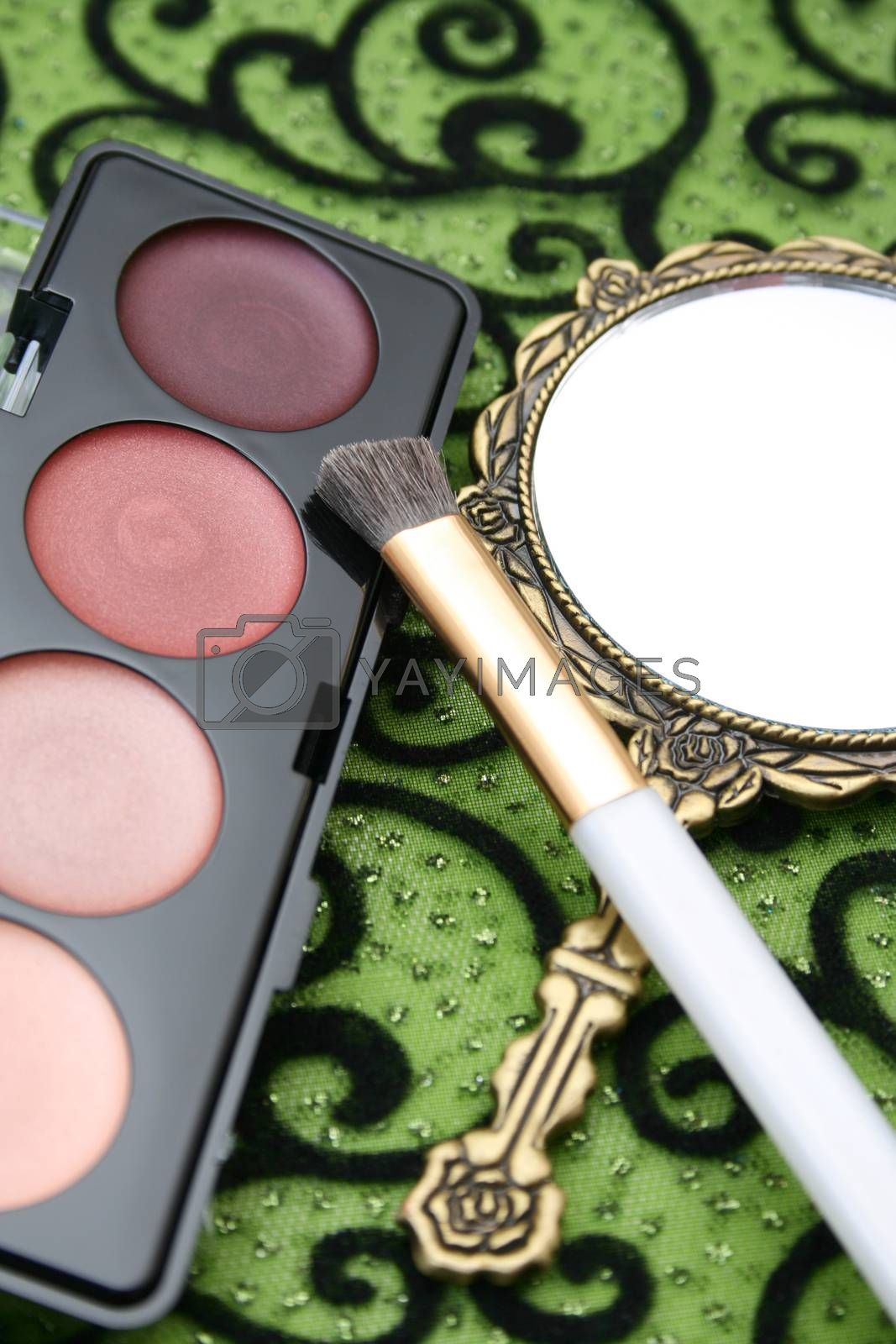 New eyeshadow set with used lipstick and small mirror.
