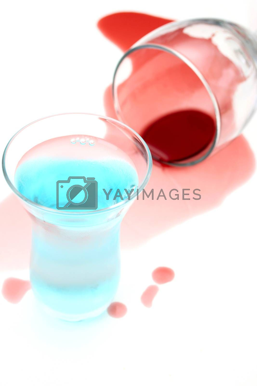 Spilled wine and a shot glass on a white background
