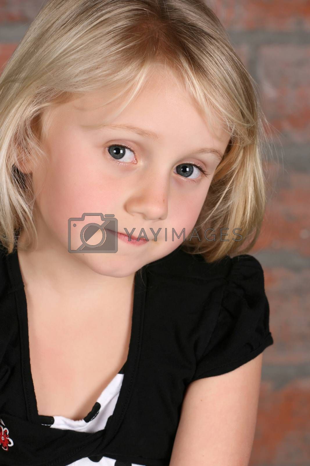 Little blond girl against a brick background